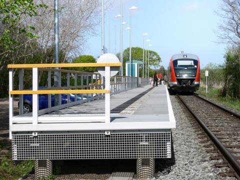 Der Zug stoppt am Bahnsteig aus GFK mit Geländer